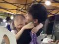 売り子の少女が男性客に抱きつき、ほっぺにチュー! 夜市で過熱する「花売り商戦」